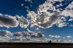 散步沿肯特海岸线的夫妇的剪影反对剧烈的平衡的天空 免版税库存照片