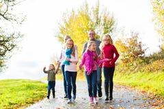 散步的家庭在秋天森林里 图库摄影