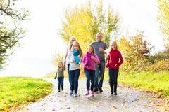 散步的家庭在秋天森林里 免版税库存照片