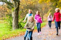 散步的家庭在秋天秋天森林里 免版税库存照片