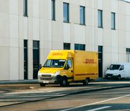 敦豪航空货运公司黄色在德国街道上的送货车 免版税库存图片