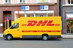 敦豪航空货运公司交付在街道上的黄色汽车 免版税图库摄影
