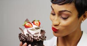 敬佩一块花梢点心杯形蛋糕的黑人妇女 免版税图库摄影