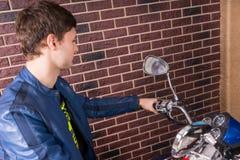 敬佩一辆停放的摩托车的年轻人 免版税图库摄影