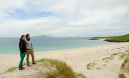 敬佩与白色沙子的年轻夫妇一个遥远的风景靠岸 库存照片