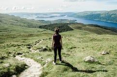 敬佩在道路的女性远足者风景 库存照片