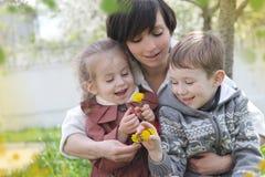 敬佩春天庭院的母亲和两个孩子 免版税库存图片