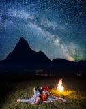敬佩难以置信地美丽的满天星斗的天空和银河和说谎在篝火附近的吐温恋人在晚上 免版税库存图片