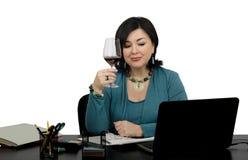 敬酒一块红葡萄酒玻璃的女实业家由Skype交谈 库存照片