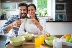 敬酒一杯咖啡的夫妇画象,当食用早餐时 免版税库存照片