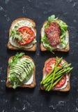 敬酒三明治用鲕梨、蒜味咸腊肠、芦笋、蕃茄和软干酪在黑暗的背景,顶视图 鲜美早餐,快餐或 库存图片