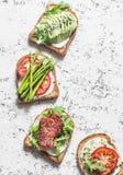 敬酒三明治用鲕梨、蒜味咸腊肠、芦笋、蕃茄和软干酪在轻的背景,顶视图 鲜美早餐,快餐o 免版税库存照片