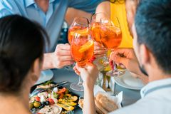 敬酒与一个刷新的夏天的快乐的朋友在一家时髦餐馆喝 图库摄影