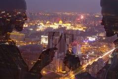 敬酒与在夜都市风景的香槟槽的夫妇两次曝光  库存图片