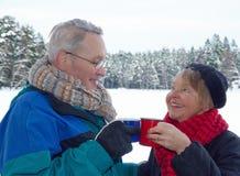 敬酒与杯子的年长愉快的夫妇温暖的饮料 免版税图库摄影