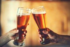 敬酒与杯的两个朋友低度黄啤酒在客栈 免版税库存图片