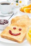 敬酒与果酱、咖啡、橙汁和新鲜的桔子微笑  图库摄影