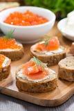 敬酒与盐味的三文鱼和红色鱼子酱在木板 图库摄影