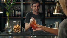 敬酒与aperol的妇女手喷鸡尾酒,酒吧作为酒精的妇女从侍酒者 影视素材