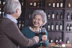敬酒和开心的资深夫妇饮用的酒,在女性的焦点 图库摄影