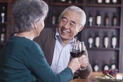 敬酒和开心的资深夫妇饮用的酒,在男性的焦点 免版税库存照片
