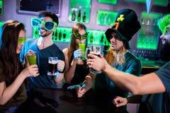 敬酒啤酒杯和饮料玻璃的小组朋友 库存图片