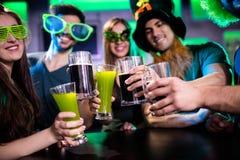 敬酒啤酒杯和饮料玻璃的小组朋友 图库摄影