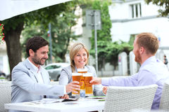 敬酒啤酒杯的愉快的买卖人在室外餐馆 免版税库存图片