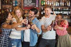 敬酒啤酒瓶的小组朋友在客栈 库存照片