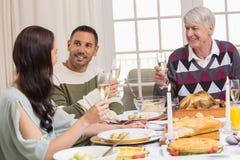 敬酒在圣诞晚餐期间的微笑的家庭 库存图片