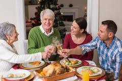 敬酒在圣诞晚餐的愉快的家庭画象 免版税库存图片