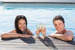 敬酒在游泳池的夫妇香槟 免版税图库摄影