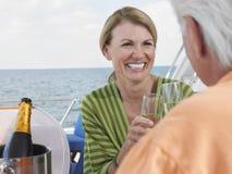 敬酒在游艇的夫妇香宾 库存图片