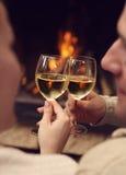 敬酒在被点燃的firep前面的浪漫年轻夫妇葡萄酒杯 免版税图库摄影