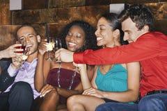 敬酒在酒吧的不同种族的朋友饮料 免版税库存图片
