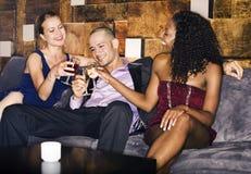敬酒在长沙发的人们饮料在酒吧 免版税库存图片