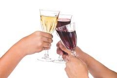 敬酒在水晶玻璃的手红色和白葡萄酒 免版税库存图片