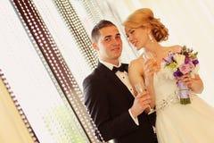 敬酒在他们的婚礼之日的新娘和新郎 免版税库存图片