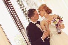 敬酒在他们的婚礼之日的新娘和新郎 免版税库存照片