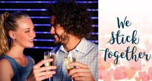 敬酒杯在酒吧的香槟的夫妇的综合图象 库存照片
