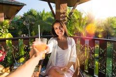 敬酒玻璃用与人的汁液的快乐的妇女一起坐夏天大阳台食用的夫妇Pov早餐  免版税库存图片
