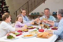 敬酒用在圣诞晚餐的白葡萄酒的家庭 免版税图库摄影