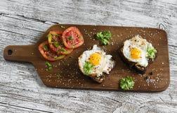 敬酒用希腊白软干酪和煎鹌鹑蛋,轻的木表面上的新鲜的蕃茄 库存图片