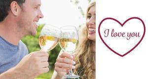 敬酒用白葡萄酒的快乐的夫妇的综合图象 免版税库存图片