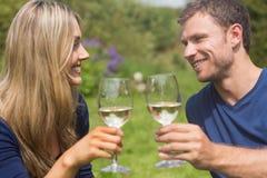 敬酒用白葡萄酒的逗人喜爱的夫妇 免版税库存照片