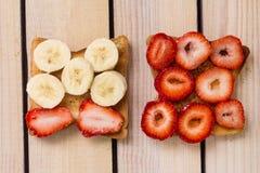 敬酒用草莓和香蕉在木背景 库存照片