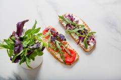 敬酒用蕃茄、芝麻菜、rucola、mozarella乳酪、面包和绿色 库存图片