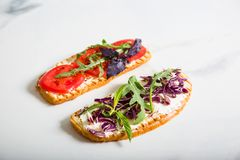 敬酒用蕃茄、芝麻菜、rucola、mozarella乳酪、面包和绿色 库存照片
