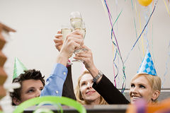 敬酒用香槟的三个办公室工作者 免版税库存照片