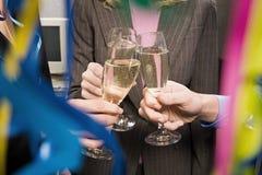 敬酒用香槟的办公室工作者 免版税库存图片